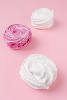 Frische vanille- und beeren-marshmallows auf einem pastellrosa hintergrund.