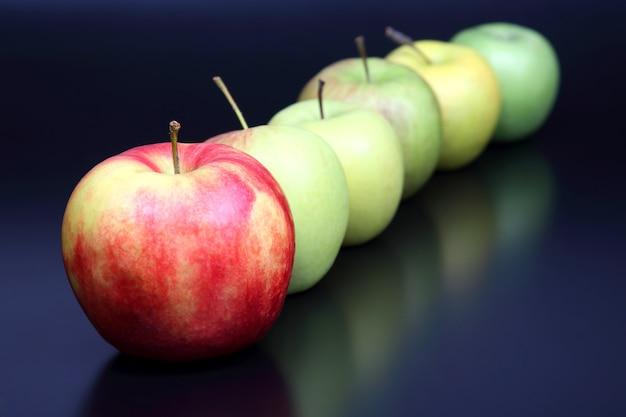Frische verschiedene äpfel auf dunklem tisch