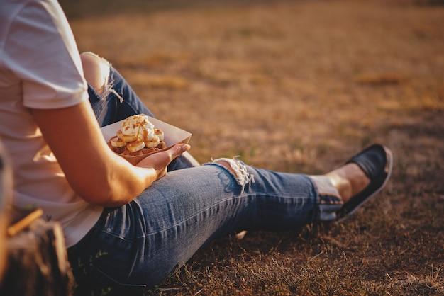 Frische waffel, die in den händen hält, amerikanisches essen zum mitnehmen. filmkorn