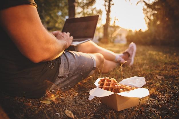 Frische waffeln in der nähe von kerl mit laptop auf dem boden, amerikanisches essen zum mitnehmen. filmkorn, getöntes bild