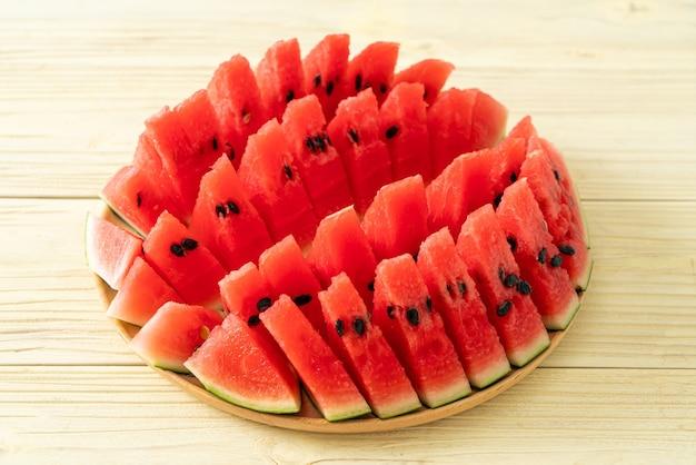 Frische wassermelone auf holzteller geschnitten