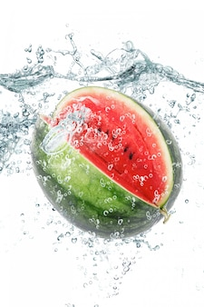 Frische wassermelone, die in wasser fällt