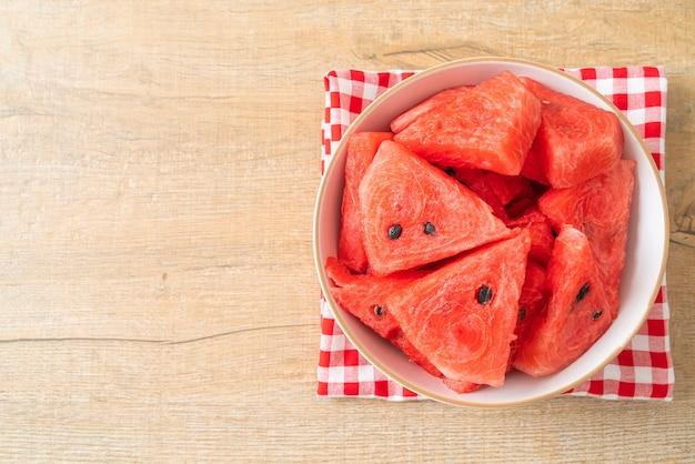 Frische wassermelone in scheiben geschnitten in weißer schüssel
