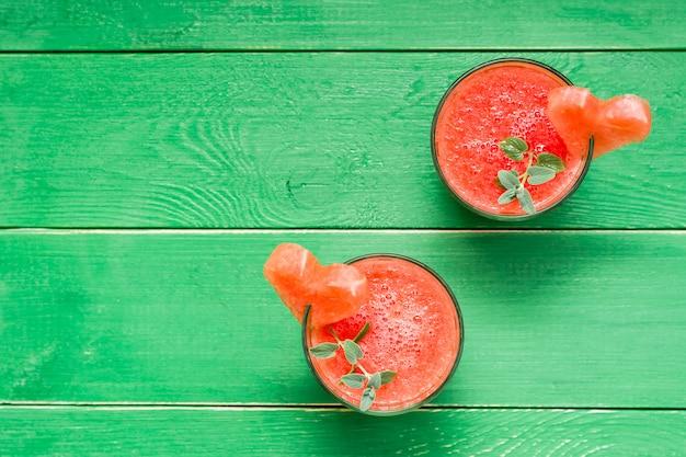 Frische wassermelone mischte getränk mit tadellosen blättern und einem herzen der wassermelone in den gläsern auf einem holztisch. ansicht von oben
