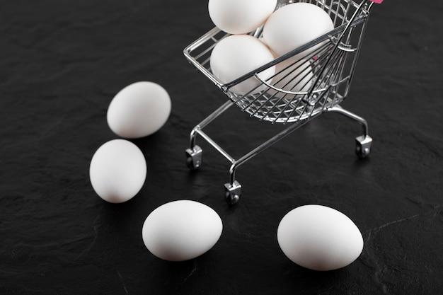 Frische weiße eier im kleinen einkaufswagen.