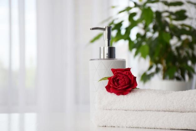 Frische weiße handtücher gefaltet auf dem tisch mit roter rose und handseifenspender mit zimmerpflanze