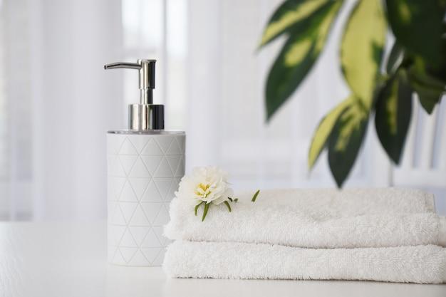 Frische weiße handtücher gefaltet auf weißem tisch, weißer blume und flüssigem behälter mit grünen blättern der zimmerpflanze und des tüllfensters auf hintergrund.