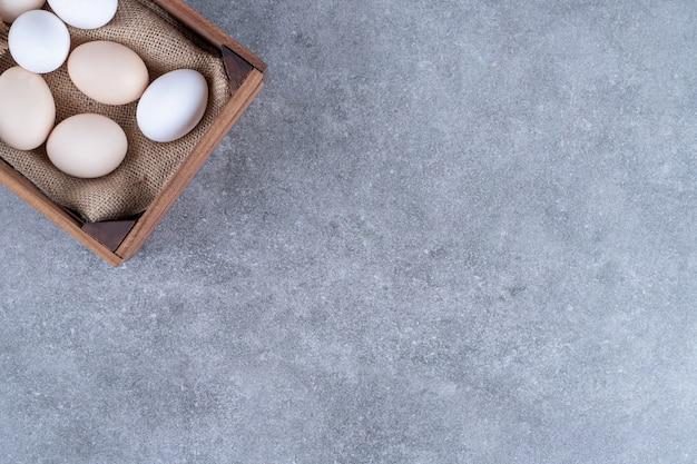 Frische weiße hühnereier auf einem holzkorb