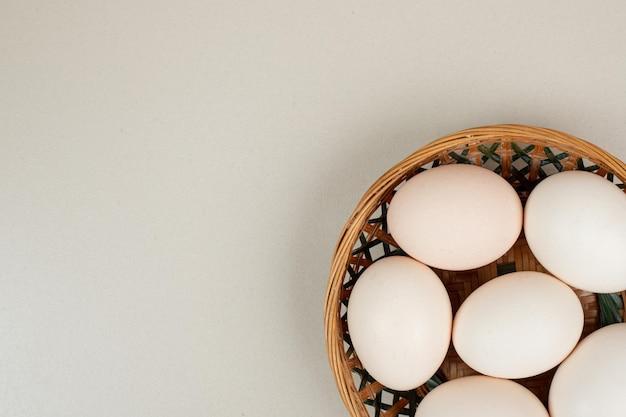Frische weiße hühnereier auf weidenkorb.