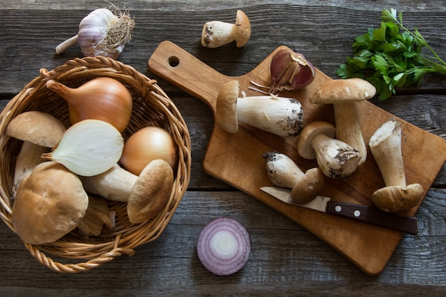Frische weiße pilze im korb und bestandteile für champignoncremesuppe auf hölzernem brett.