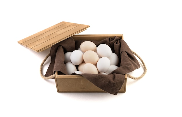 Frische weiße und braune hühnereier werden in eine holzverpackung mit deckel gelegt.