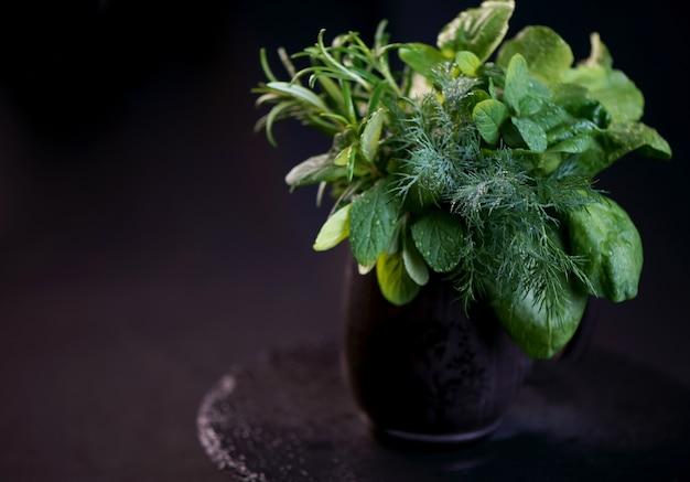 Frische würzige kräuter - minze, rosmarin, dill, rucola und spinat in einer schwarzen tasse auf schwarzer oberfläche
