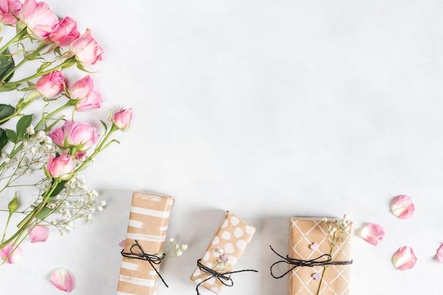 Frische wunderbare blumen in der nähe von geschenken und blütenblättern
