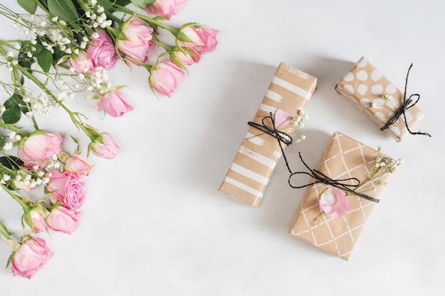 Frische wunderbare rosen in der nähe von geschenkboxen und blütenblättern