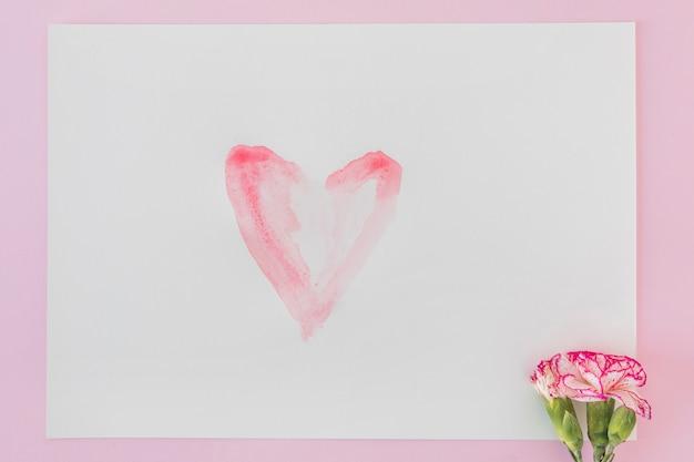 Frische wundervolle blüte und papier mit gemaltem herzen