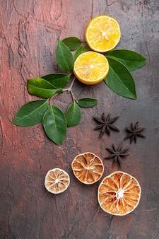 Frische zitrone der draufsicht mit grünen blättern auf dunklen früchten des dunklen tischfotos