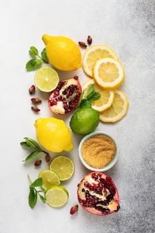 Frische zitrone, limette, granatapfel, getrocknete tee rosenblüten, tee, rohrzucker und blätter minze bouquet auf grau. zutaten für die zubereitung von limonadengetränken, mahito oder kaltem, erfrischendem tee.
