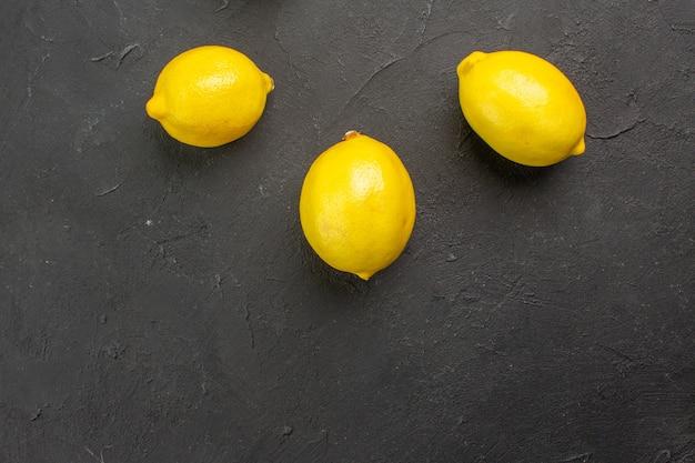 Frische zitronen der draufsicht, die auf dunklem zitrusgelbfruchtkalk des tisches ausgekleidet sind