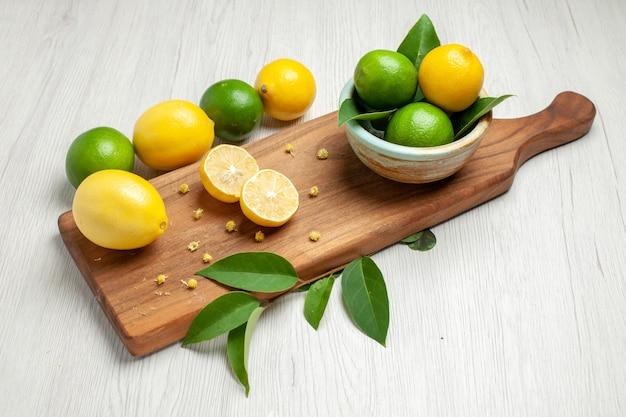 Frische zitronen der vorderansicht auf frischem saurem saft der weißen zitrusfrucht der tabelle
