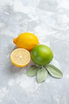 Frische zitronen der vorderansicht saftig und sauer auf tropischen exotischen fruchtzitrusfrüchten des weißen schreibtisches