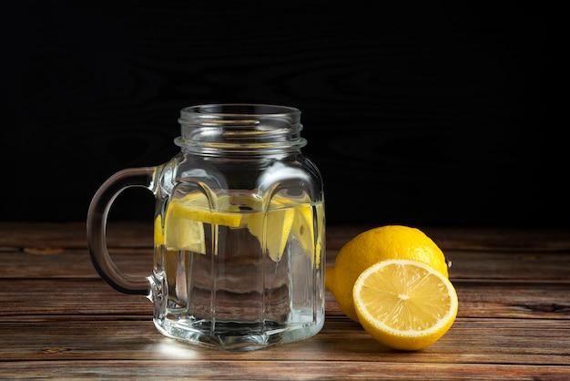 Frische zitronen und eine tasse reines wasser