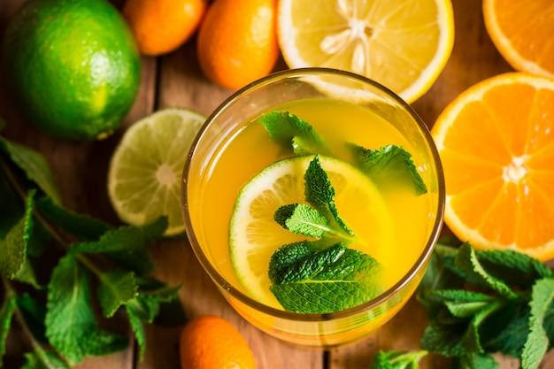 Frische zitronenlimonade von der orangenkalkminze im glasfrühlings-detox, auffrischungsgetränk