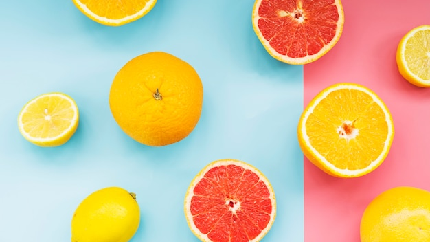 Frische zitrusfrüchte auf doppeltem buntem hintergrund