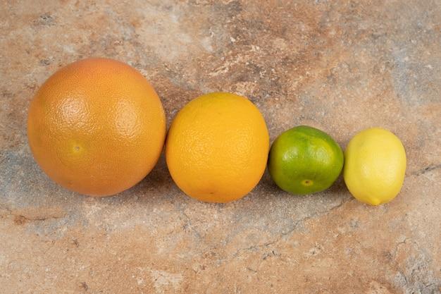 Frische zitrusfrüchte auf marmorhintergrund.