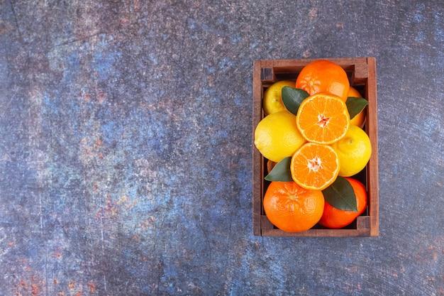 Frische zitrusfrüchte mit blättern in einer alten holzkiste.