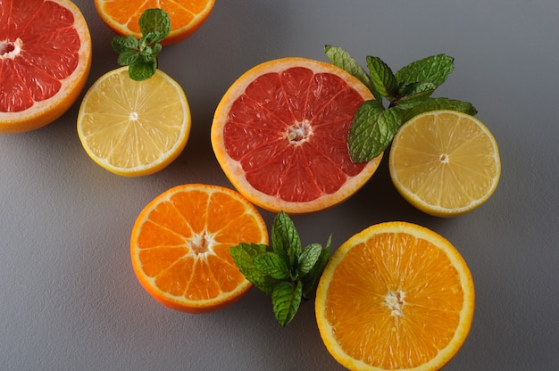 Frische zitrusfrüchte und minze halbieren auf grauem hintergrund. saftige grapefruits, mandarinen, zitronen, orangen. zitronensaft zutaten, lebensmittel hintergrund