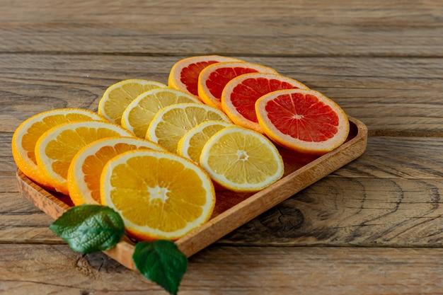 Frische zitrusfrüchte zitrone orange und limette mit blatt auf holztablett, detailansicht. bio zitrusfrüchte.
