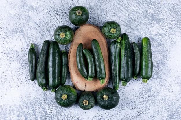 Frische zucchini auf einem stummel und flach lagen auf einem grau strukturierten tisch