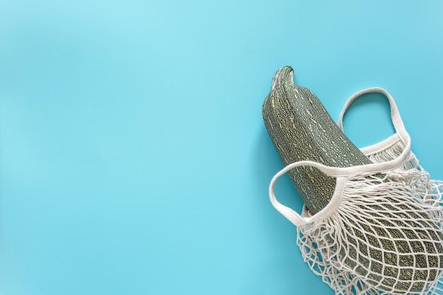 Frische zucchini in der wiederverwendbaren kaufenden umweltfreundlichen maschentasche auf blauem hintergrund
