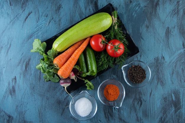 Frische zucchini, karotten, tomaten und grüns auf schwarzem teller mit gewürzen.