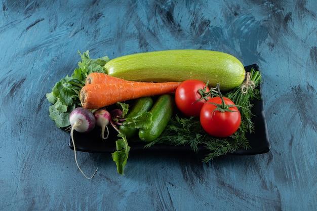 Frische zucchini, karotten, tomaten und grüns auf schwarzem teller.