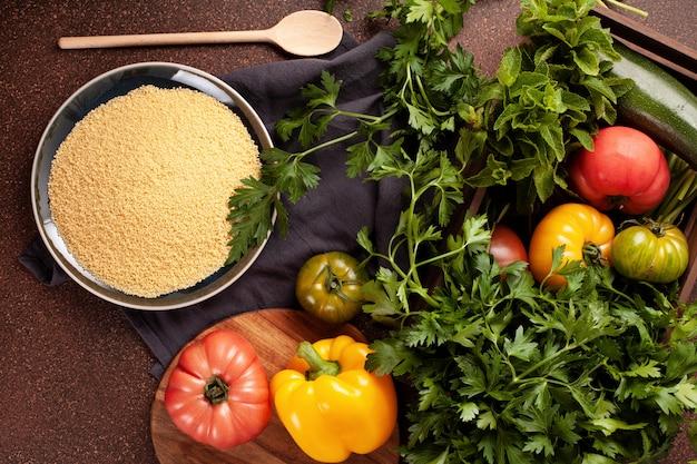 Frische zutaten für taboulé-salat: couscous, tomaten, zitrone, petersilie, minze, olivenöl, paprika. gesundes, vegetarisches halal nahrungsmittelkonzept
