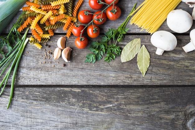 Frische zutaten zum kochen von nudeln, tomaten und gewürzen über holztischhintergrund mit kopierraum