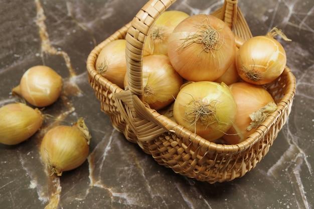Frische zwiebeln in einem weidenkorb. korb mit frischen zwiebeln. nahansicht