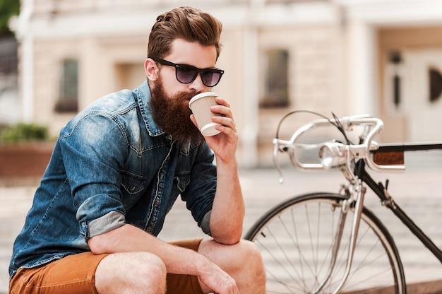Frischen kaffee genießen. selbstbewusster junger bärtiger mann, der kaffee trinkt und in die kamera schaut, während er im freien in der nähe seines fahrrads sitzt sitting