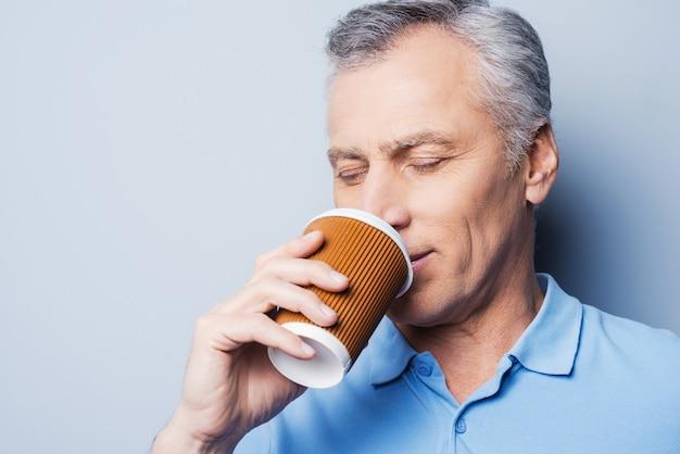 Frischen kaffee trinken. hübscher älterer mann, der eine tasse kaffee hält und die augen geschlossen hält, während er vor grauem hintergrund steht