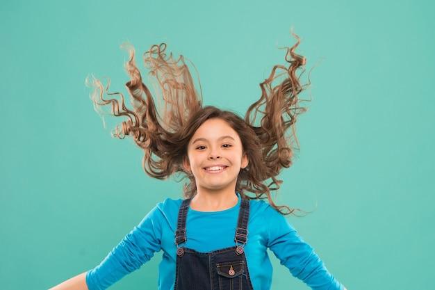Frischen sie es auf. starkes und gesundes haarkonzept. schöne und ordentliche frisur. einfache tipps für frisuren für kinder. kleines kind langes haar. mädchen aktives kind mit langen herrlichen haaren. extra frisches trockenshampoo.