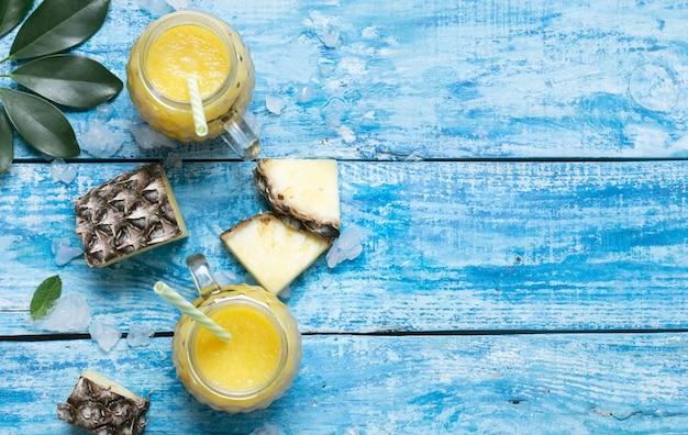 Frischer ananas-smoothie in gläsern mit strohhalmen auf einem blauen rustikalen hölzernen hintergrund
