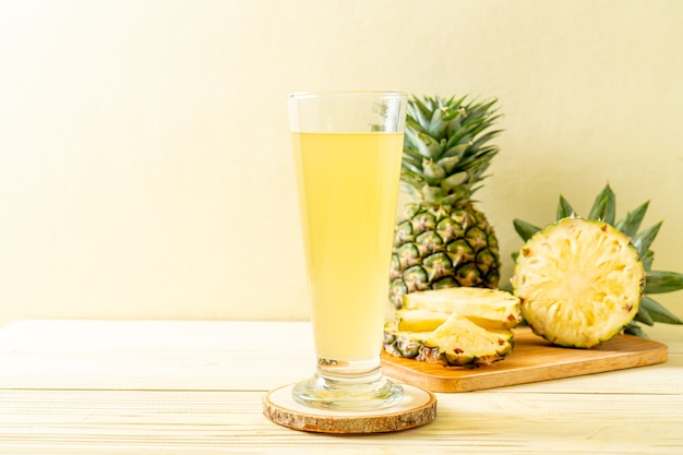 Frischer ananassaft mit ananas auf holzoberfläche