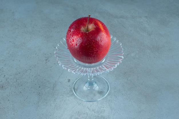 Frischer apfel auf einem glassockel, auf dem marmorhintergrund. foto in hoher qualität