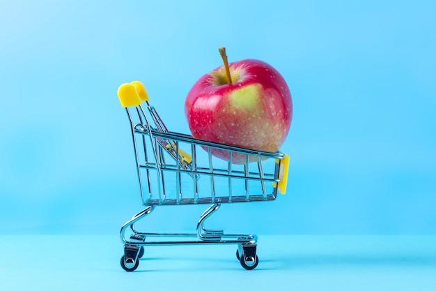 Frischer apfel in einem einkaufswagen. diät-konzept. planen sie, in form zu kommen, sport zu treiben und zusätzliche kilogramm zu verlieren