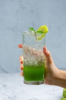 Frischer apfelsaft in einem glas mit grünen äpfeln.