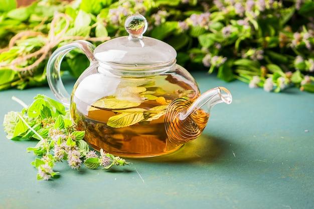 Frischer aromatischer tee mit glasteekanne der melisse-minze verlässt auf holz