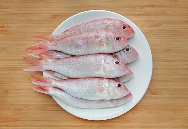 Frischer aufwändiger threadfin brachsen auf weißer platte gegen hintergrund des hölzernen brettes.
