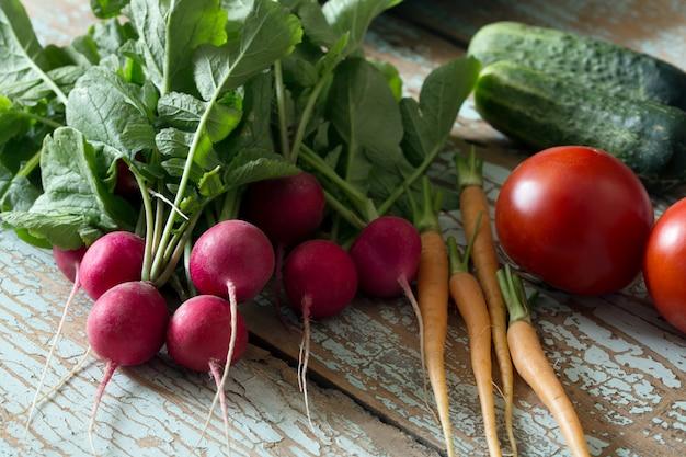 Frischer bauernhofgemüserettich, gurke, tomate, karotte auf hölzerner rustikaler, seitenansicht