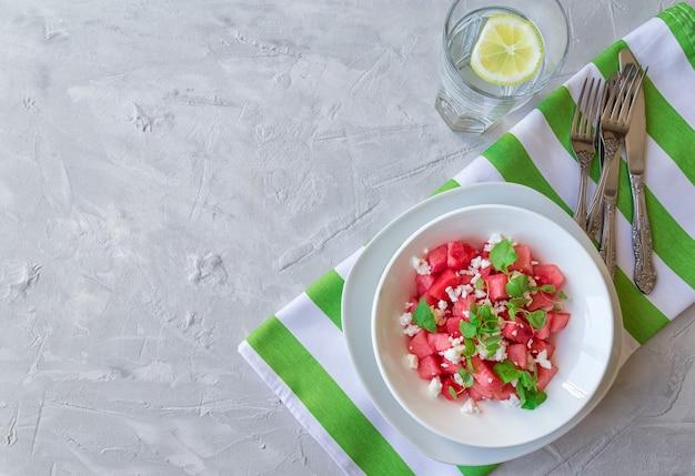 Frischer bio-salat mit wassermelone, feta-käse und minze auf hellgrauem betonhintergrund. gesundes vegetarisches essen. draufsicht. speicherplatz kopieren.